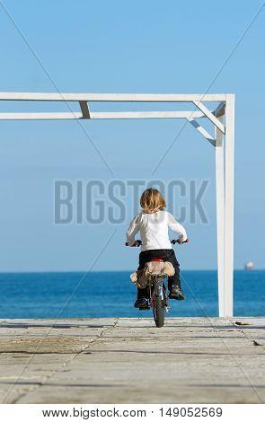 Cute boy with bike on the beach. Bulgaria Burgas autumn