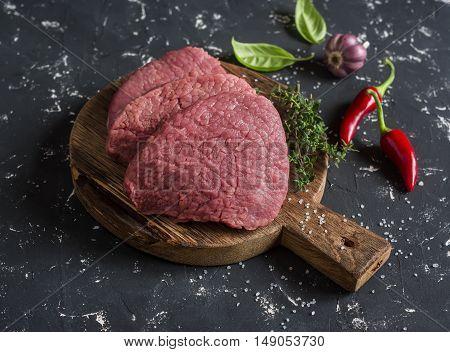 Raw beef chops on a wooden cutting board on a dark background