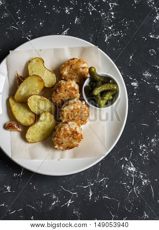 Fish balls and baked potatoes on light plate on dark background