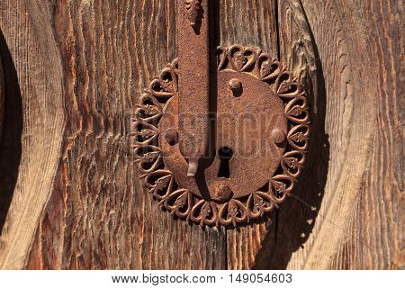 Ornate Rusty door keyhole background with distressed wood