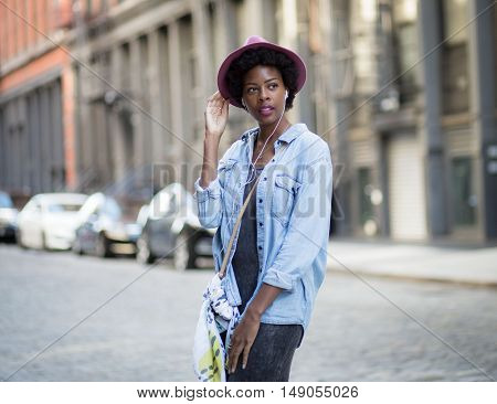 Portrait of young African American woman standing on city street. Photographed in Soho NYC.
