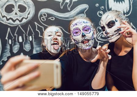 Three girls going on Halloween, grimace make selfie on a dark background with a pattern