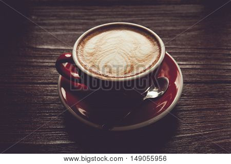 Vintage tone of coffee in red cup on wooden vintage table