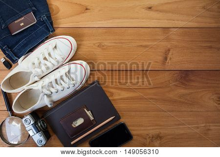 Outfit of traveler student teenager young woman or guy. Overhead of essentials for modern young person. Different objects on wooden background.