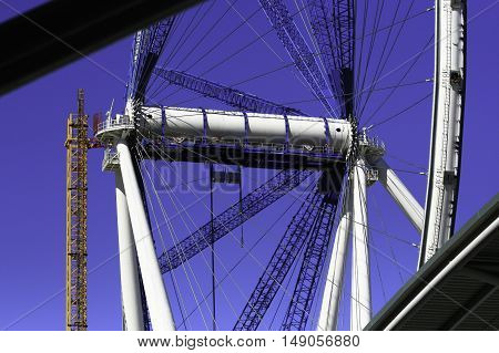 A very large ferris wheel under construction against a blue sky