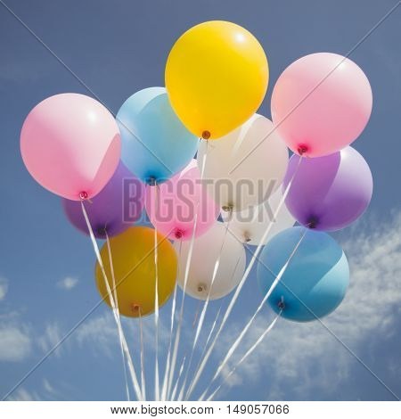 Vintage tone of Colorful party balloon floating in mid air against a bright blue sky.