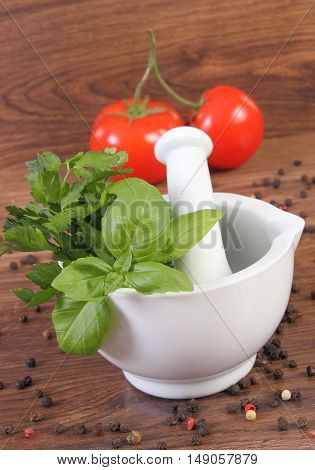 Parsley With Basil In Mortar And Colorful Pepper On Rustic Boards