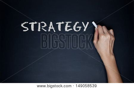 Strategy - female hand with chalk and arrow with text