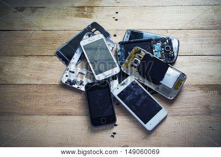 Broken smart phone with space in wooden texture background