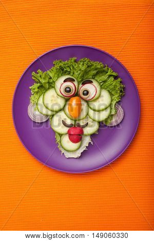 Funny face made of vegetables on plate and fabric