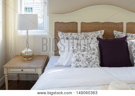 Vintage Bedroom Interior With Flower Pillows And Decorative Table Lamp