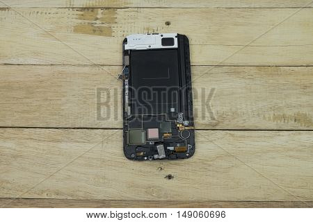 Broken smart phone with space in wooden texture background