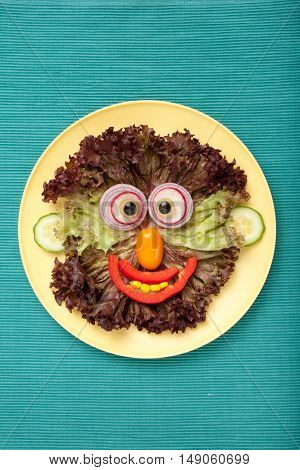 Funny smiling face made of vegetables on plate and fabric