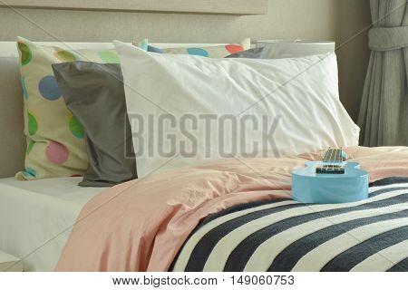 modern bedroom with light blue ukulele on striped bedding