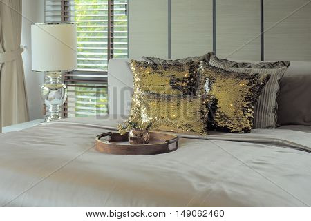 Wooden Tray With Golden Glitter Pillows On Bed
