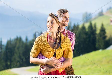 Couple in Tracht on Alp mountain summit at vacation
