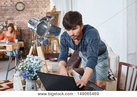 Young man using laptop computer at home.