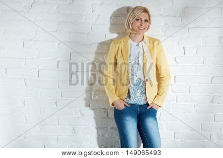 Casual young blonde woman standing by white brick wall with hands in pockets, smiling.