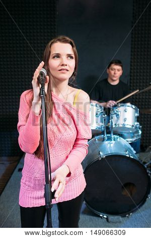 Female singer on stage holding microphone. Woman soloist ready to sing a song, music band performance. Hobby, pastime, show, leisure concept