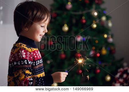 Beautiful Little Child Holding Burning Sparkler On New Year's Eve