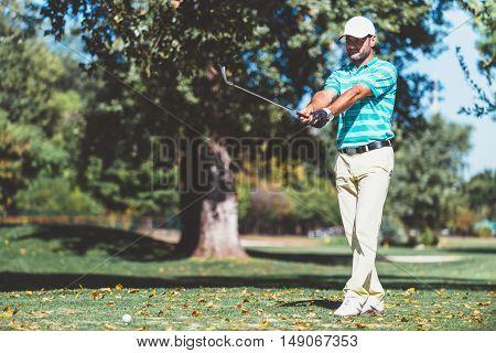 Golfer planing ball trajectory, toned image, horizontal image, green