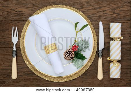Christmas dinner table setting with white porcelain plate, holly, napkin and ring, vintage cutlery, cracker, holly, mistletoe, fir and pine cone on gold mat over dark wood background.
