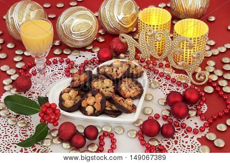 Christmas still life with florentine biscuits, gold glitter noel sign, eggnog, holly, candles and decorations on a red background.
