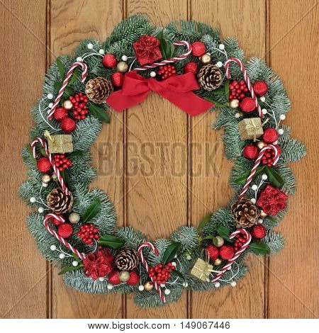 Christmas fir wreath decoration with candy canes, red and gold bauble and gift box decorations, holly, mistletoe and pine cones on oak front door background.