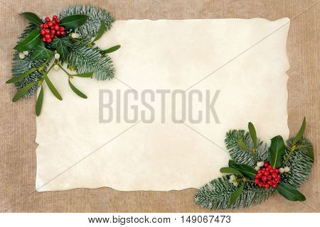 Traditional winter and christmas background border of flora of holly, ivy, mistletoe and snow covered leaf sprigs  on parchment and hemp paper.