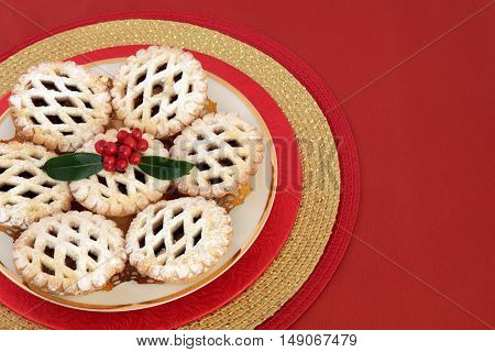 Christmas latticed mince pie cakes with holly on a red background with copy space.