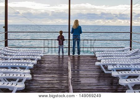 Mother and daughter standing on the pier, around the empty and rain watered the sunbeds. Out of the beach season and it was cold.