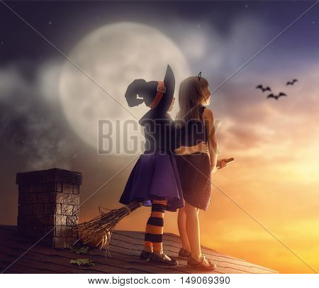 Two happy sisters on Halloween. Funny kids in carnival costumes on the roof with broomstick. Cheerful children looking at moon.