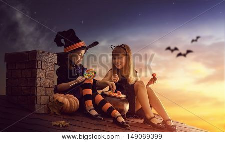 Two happy sisters on Halloween. Funny kids in carnival costumes sitting on the roof. Cheerful children with pumpkin and candy.