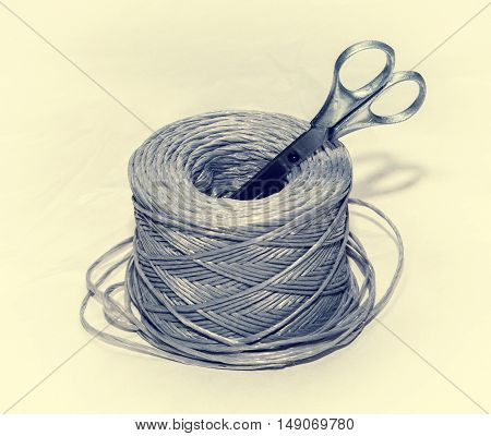 coil of rope and scissors on a white background a roll of twine binding household