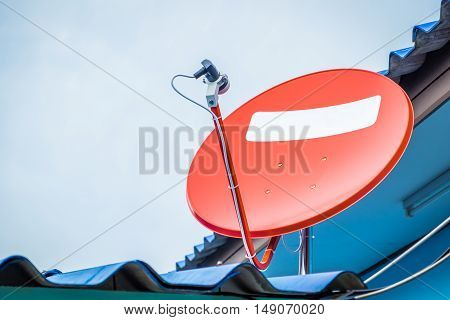 Satellite TV antenna on blue sky background.