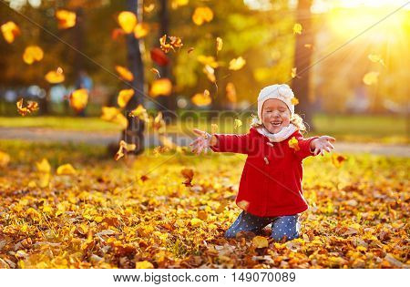happy child girl laughing and playing leaves in autumn outdoors
