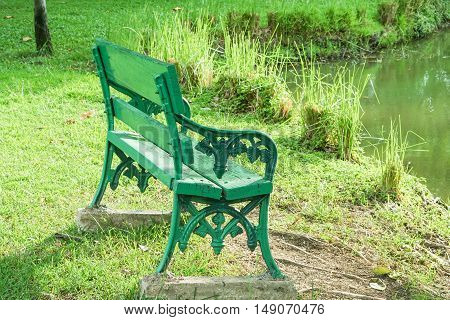 Green bench for sitting at riverside in the park