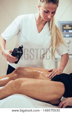 Sports Massage - Female Physical Therapist Massaging Man