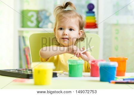Cute little child girl painting with paintbrush and colorful paints