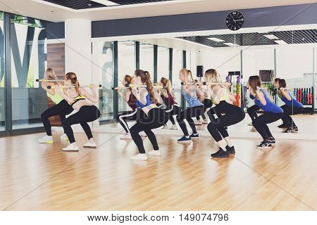 Squats with weights on training. Group of young women in aerobics class making exercises. Girls do squats with barbells. Healthy lifestyle in fitness club. View from back side