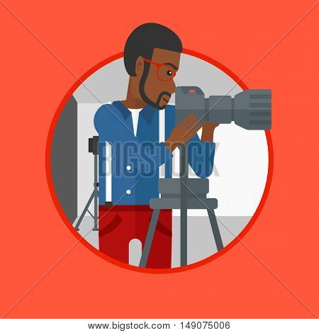 An african-american photographer working with camera on a tripod in photo studio. Photographer using camera in the studio. Vector flat design illustration in the circle isolated on background.