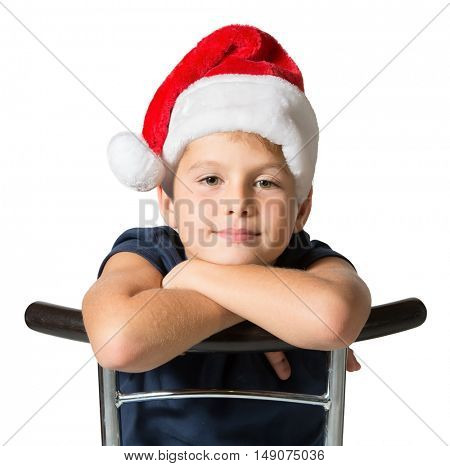 Charming seven year old boy in red Santa hat cheerfully smiles. Photo executed on a white background