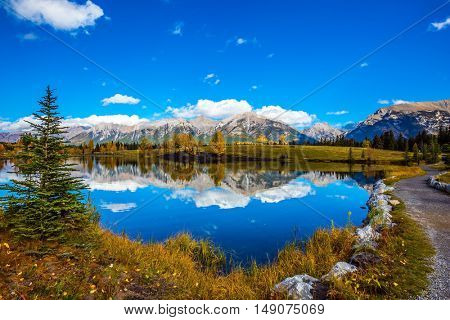 Path around the lake. Canmore, near Banff National Park. Majestic mountains and scenic cumulus clouds are reflected in the water. The concept of recreational tourism