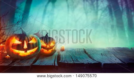 Halloween background. Spooky forest with dead trees and pumpkins.Halloween design with pumpkins