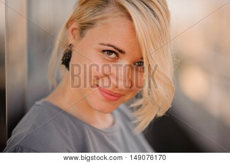 Portrait of young beautiful blond woman outdoors looking in camera