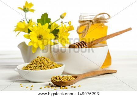 the jar of honey near two bowls one with of pollen another with honey and flower on white table