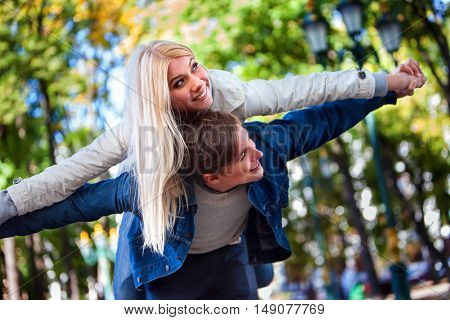 Young couple in love on romantic date flirt in park. Girl in love embraces guy for shoulders in autumn park.