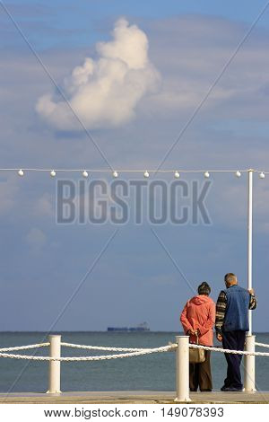 Elderly couple on pier. Grandparents looking at ship at sea under big cloud. Beautiful seascape with cloudy sky