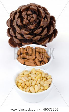 Stone pine cone with seeds and nuts over white. Geometric Pinophyta cone, seeds, nutshells and shelled nuts in white bowls in a row. Close up macro food photo from above on white background.