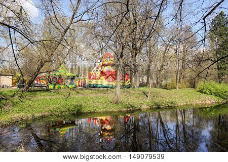 Children's attractions in the park on the shore. Nature in early spring in city park.
